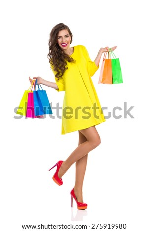 Fashion Shopping. Smiling elegance young woman in red high heels and yellow mini dress holding colorful shopping bags. Full length studio shot isolated on white. - stock photo