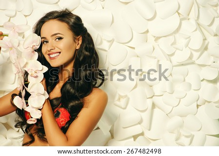 Fashion shot of a beautiful brunette woman in bikini posing over background of white paper flowers. Beauty, fashion. Spa, healthcare.  - stock photo