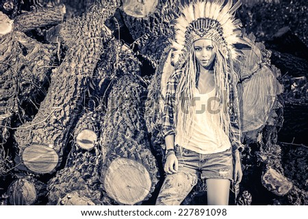 Fashion shot of a beautiful girl in style of the American Indians. Western style. Jeans fashion. Toned photo. - stock photo