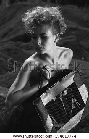 Fashion shot of a beautiful, professional model with a bag in her hands.Blonde beauty with bag posing outdoor.Fashion colors.