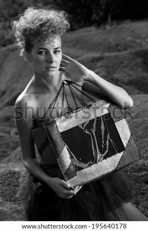 Fashion shot of a beautiful, professional model with a bag in her hands.Blonde beauty with bag posing outdoor.B&W.