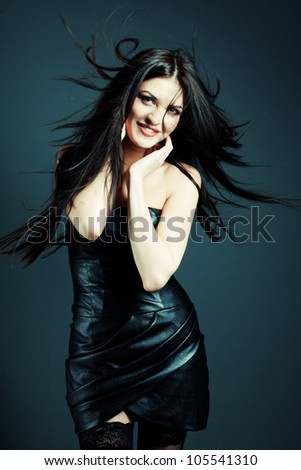 Fashion shot of a beautiful sexy girl in leather fashionable dress in the studio. Hair waving wind - stock photo