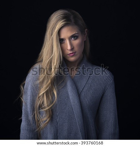 Fashion shot of a beautiful woman in a grey sweater on a black background