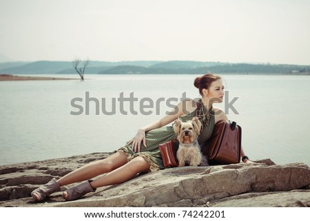 Fashion shot of a beautiful woman lying on the shore of the lake with a suitcase and a dog (Yorkshire terrier) - stock photo