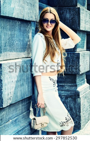 Fashion shot of a beautiful woman standing on the city street. Elegant businesswoman outdoor.  - stock photo