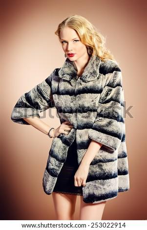 Fashion shot of a beautiful young woman wearing fur coat. Studio shot. - stock photo