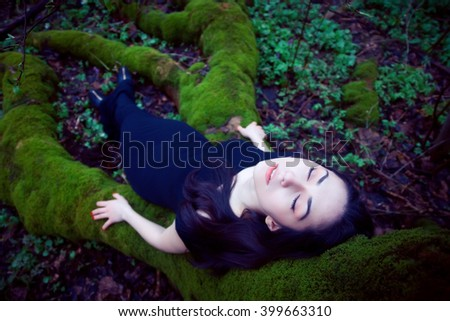 Fashion shot of a dark-haired beautiful woman lying on a moss-covered big tree roots. The young woman is a very beautiful and attractive. The girl is dressed in black dress. She is carefree and serene - stock photo