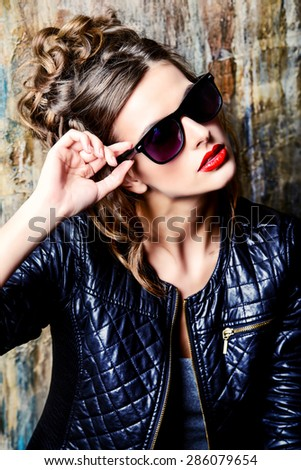 Fashion shot of a gorgeous young woman wearing black leather jacket and sunglasses. - stock photo
