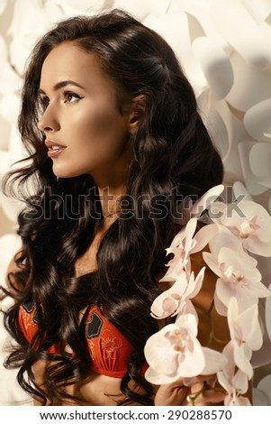 Fashion shot of a gorgeous  young woman with beautiful long hair posing over background of white paper flowers. Beauty, fashion. Spa, healthcare.  - stock photo
