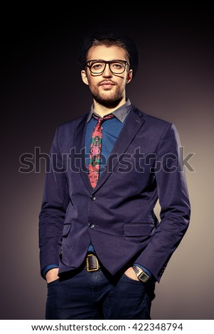 Fashion shot of a handsome man wearing elegant suit and spectacles. Men's beauty, fashion. Business style.