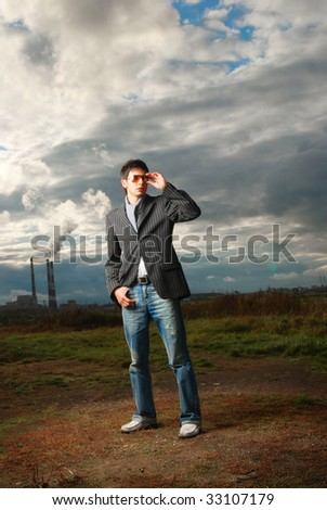 Fashion shot of a handsome young man that stays at the field, he is in glasses. Outdoor.