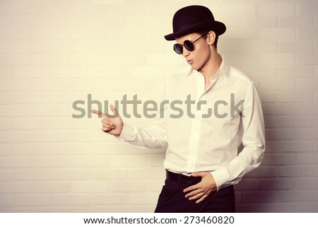 Fashion shot of a modern young man in white shirt, black bowler hat and round sunglasses.  - stock photo