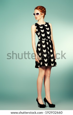 Fashion shot of a pin-up girl posing at studio. Full length portrait. - stock photo