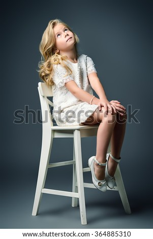 Fashion shot of a pretty little girl with beautiful blonde hair wearing white dress. Studio shot. Kid's beauty, fashion. - stock photo