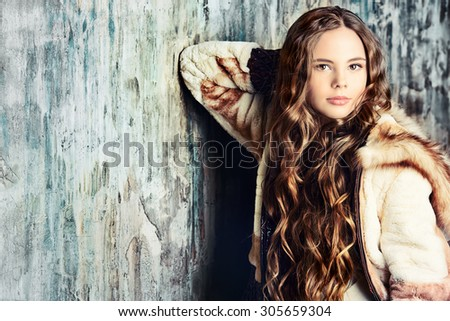 Fashion shot of a pretty teenager girl with beautiful long curly hair wearing fur coat. Beauty, fashion. - stock photo