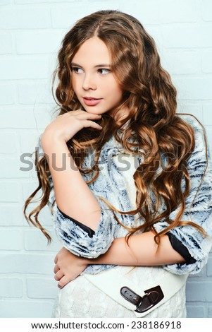 Fashion shot of a pretty teenager girl with beautiful long curly hair wearing white knitted dress and fur jacket. Beauty, fashion. - stock photo