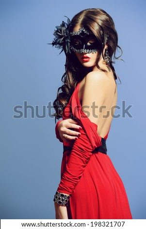 Fashion shot of a sexual  woman in elegant red dress with bare shoulder wearing ornate carnival mask.