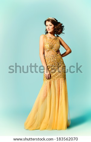 Fashion shot of a stunning woman in luxurious golden dress. Full length portrait.