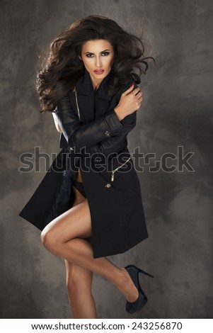 Fashion shot of a woman in black coat  - stock photo