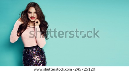 Fashion shot of a woman in pink top and glitter skirt  - stock photo