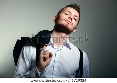 Fashion Shot of a young man hold coat. He is now a professional model - stock photo