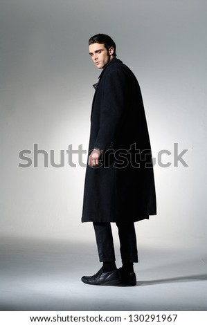 Fashion Shot of a young man in black coat posing on light background
