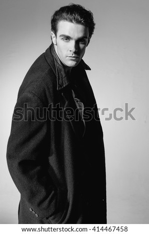 Fashion Shot of a young man in coat on light background