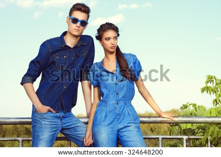 Fashion shot of an attractive young couple in jeans clothes posing outdoor.  - stock photo