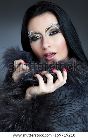 Fashion shot of beautiful woman with jewelry make-up and coat