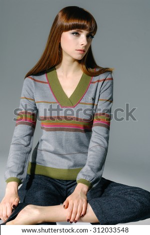 fashion shot of girl sitting posing in light background  - stock photo