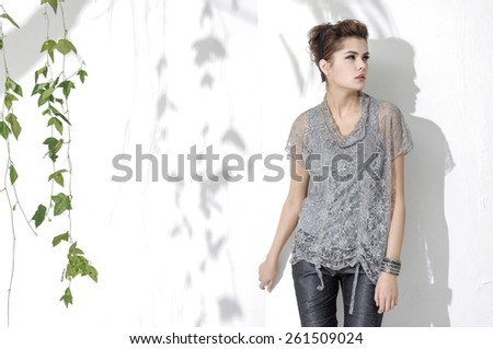 fashion shot of girl with green ivy posing in light background  - stock photo