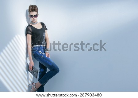 fashion shot of girl with sunglasses holding purse posing in light background  - stock photo