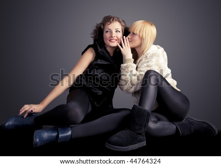 Fashion shot of two attractive young women telling secrets