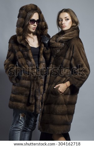 Fashion shot of two elegant beautiful girls (brunette and blonde) in studio on grey background wearing sunglasses and furs coat . Shopping inspiration - stock photo