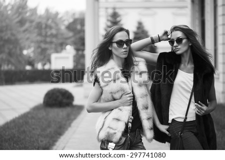 Fashion shot of two elegant beautiful girls in the sunset wearing sunglasses, fur vests . Two young women outdoor on the street. Shopping inspiration. Black and white concept - stock photo