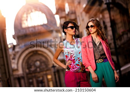 Fashion shot of two elegant beautiful girls in the sunset wearing sunglasses. Two young women outdoor on the street. Shopping inspiration - stock photo
