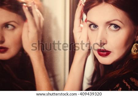 Fashion shot of young beautiful woman in black dress staying near mirror. Woman stays near mirror. - stock photo