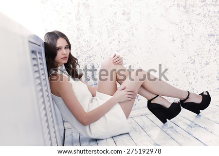 Fashion shot of young beautiful woman in white short dress and black shoes - stock photo
