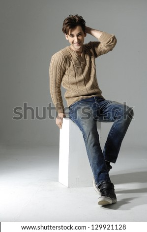 Fashion Shot of young man sitting cube. He is now a professional model. - stock photo