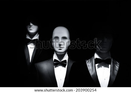 fashion showcase men models in black dress suit isolated on black background - stock photo
