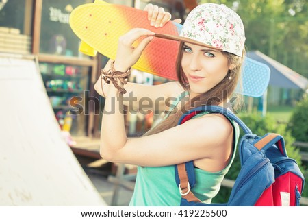 Fashion skateboarder young woman with a skateboard. Adventure at summer trip. Sport. Girl dressed in cap, wearing backpack. Accessories