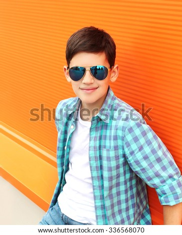 Fashion smiling child boy wearing a sunglasses and shirt in city - stock photo