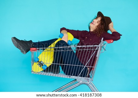 Fashion smiling hipster woman having fun wearing a hat with yellow skateboard sitting in the shopping trolley cart isolated over blue background - stock photo