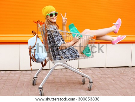 Fashion smiling hipster woman having fun wearing a sunglasses with skateboard and backpack sitting in the shopping trolley cart outdoors - stock photo