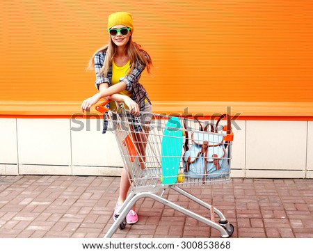 Fashion smiling hipster woman wearing a sunglasses and colorful clothes with skateboard and backpack in shopping trolley cart outdoors - stock photo