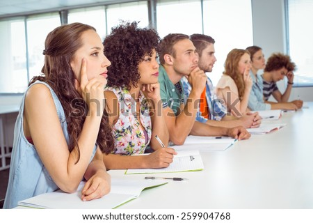 Fashion students being attentive in class at the college - stock photo