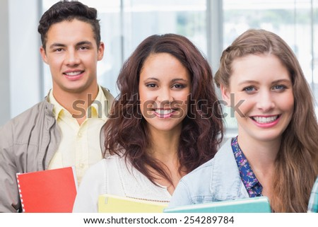 Fashion students smiling at camera together at the college