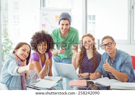 Fashion students smiling at camera together at the college - stock photo