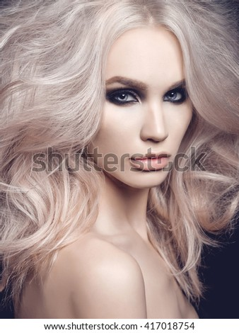 Fashion studio photo of beautiful blonde woman with smoky eyes makeup - stock photo