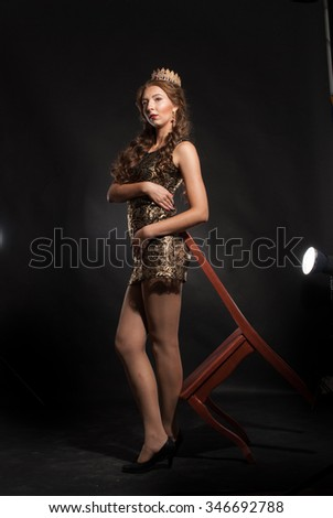 fashion studio photo of beautiful brunette woman with bright makeup wearing crown and luxurious costume of queen